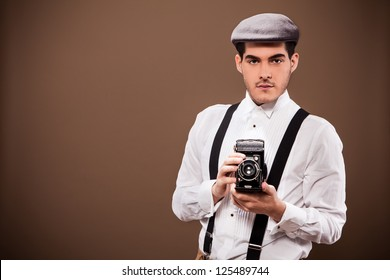 Photo of cute guy with old dslr camera and old outfit from the 30s