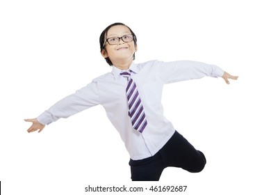 Photo of a cute little boy playing in the studio while wearing formal suit and glasses, isolated on white background