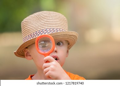 Photo of cute little happy Caucasian boy with a straw hat holding magnifying glass