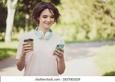 Photo of cute lovely young lady walk garden headphones neck hold mobile browse social media cheap easy communication youngster activities advert concept wear pink t-shirt park outdoors