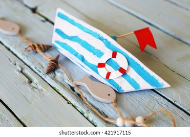Photo of cute origami paper boat on wooden backgrond