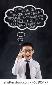 Photo of a cute schoolboy learns many language and say Hello in different languages, shot in the class