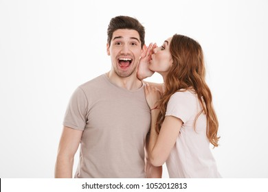 Photo of cute woman with beautiful long brown hair saying excited rumors in ear of her boyfriend or male friend isolated over white background