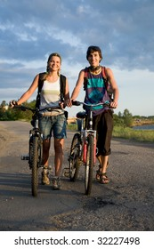 Photo of cyclists with bikes walking down country road during summer vacations