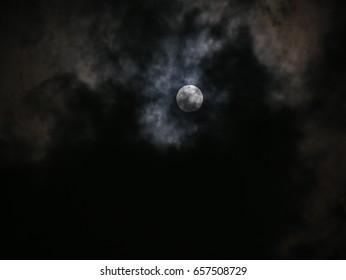 Photo of dark night full moon behind clouds, defocused background.