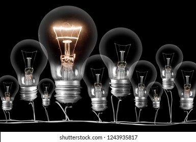 Photo of dark and shining light bulbs; concept of idea, innovation, uniqueness and standing out; isolated on black background