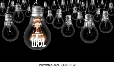 Photo of dark and shining light bulbs with fiber in Idea shape; concept of idea, innovation, uniqueness and standing out; isolated on black background