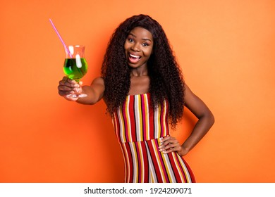 Photo of dark skin cheerful woman hold hand waist cocktail drink cheers isolated on orange color background