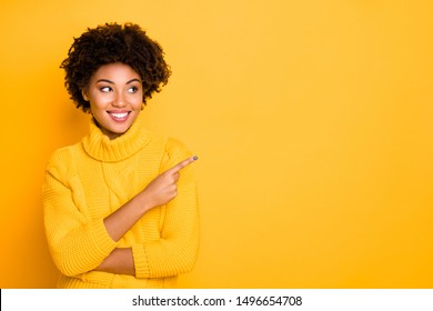 Photo of dark skin lady indicating finger empty space wear warm knitted pullover isolated yellow background
