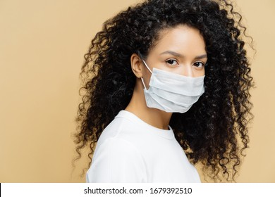Photo of dark skinned Afro American woman with curly bushy hair, wears protective mask during coronavirus covid-19 outbreak, isolated on beige background. Prevent disease. Virus, influenza, health car