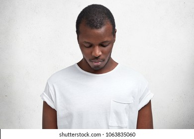 Photo of dark skinned male looks down as notices something, dressed in casual t shirt, advertizes new outfit, isolated over concrete wall. African American man poses indoor focused on floor.