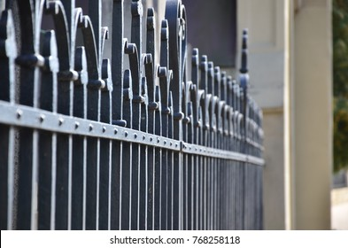 Photo of a decorative metal fence from the cemetery. Selective focus and shallow depth of field