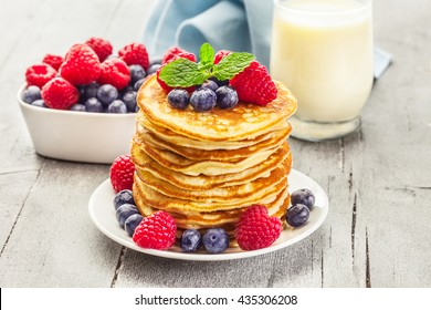 Photo  of delicious pancakes with berries over wooden table