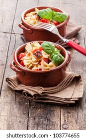 photo of delicious pasta with cherry tomatoes and olives on wooden table