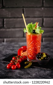 photo of delicious tomato bloody mary cocktail on reflecting stone table with spot light