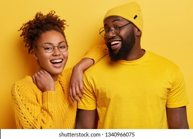 Photo of delighted cheerful young Afro American woman and man smile broadly, satisfied with good result of common work, dressed in yellow outfit, pose indoor, express good emotions. Monochrome