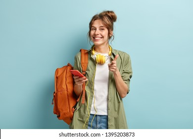 Photo of delighted European woman points at you happily, holds smartphone device connected to headphones, uses music app, smiles gladfully, dressed in long casual shirt, stands with rucksack