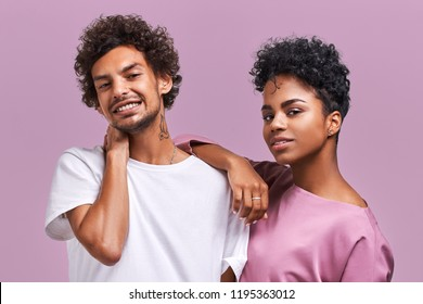 Photo of delighted girlfriend and boyfriend with dark skin, smile happily as spend weekend together, going on picnic with friends, have good relationships, dressed casually. African American couple