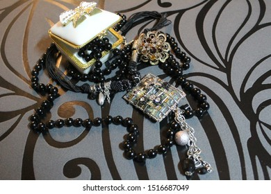 Photo depicting a white open casket with jewelry in black on a black background.