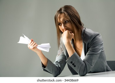 Photo of depressed female with neglected hair looking at paper in her hand and grieving