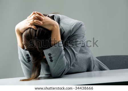 Photo of depressed female sitting at workplace and grieving