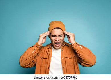 Photo of depressed mixed race man in yellow outfit, wearing hat and holding his head and screaming isolated over blue background