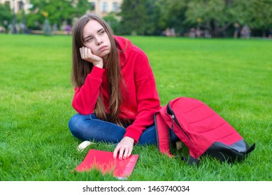 Photo of depressed passive sad teen girl sitting on green grass lawn is not willing to do home task looking away leaning on hand