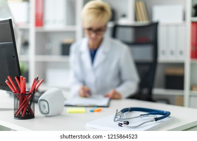 Photo with depth of field, highlighted focus on the phonendoscope. A young girl in a white robe sitting at the table and fills out a document