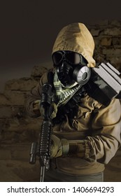 Photo of a desert post-apocalyptic soldier in tactical jacket, gas mask, gloves, rifle and armor standing on shaded wasteland background front view.