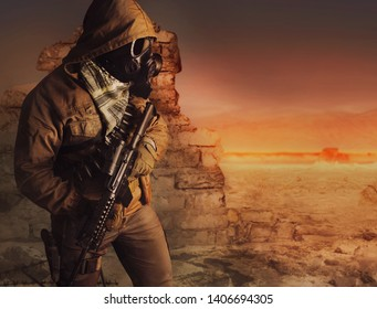 Photo of a desert post-apocalyptic soldier in tactical jacket, gas mask, gloves, rifle and armor standing on evening sunset wasteland background side view.