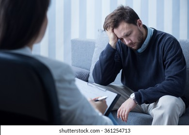 Photo of despair man during therapy with psychiatrist