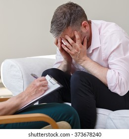 Photo of despair young male with female therapist