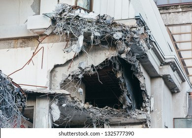 Photo of destroyed building, protruding reinforcement/ demolition of a building, house ruins, reconstruction, bricks and metal/ hole in the corner of the building, abandoned hotel,multi-storey bldng.