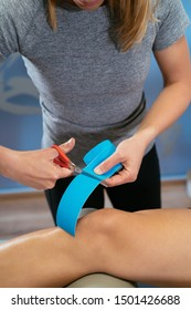Photo detail of a physiotherapist cutting blue medical tape on a patient's knee. Concept of muscle health and relaxation. Vertical image