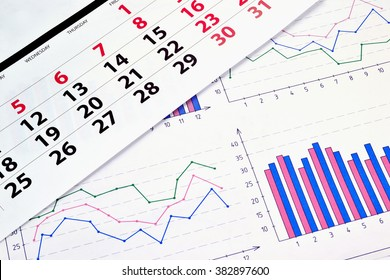 Photo diagrams and graphs on the paper with a monthly calendar