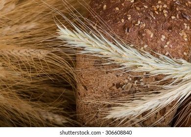 Photo different types of bread with cereals on a fabric background brown color.