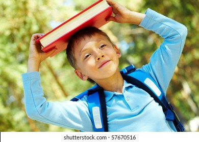 Photo of diligent schoolboy with book on his head outdoor