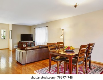 Photo of a dining space with pale yellow walls , wooden dining table set atop red rug and  wood laminate flooring. Northwest, USA