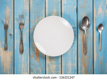 Photo of a dinner set on a blue wooden board