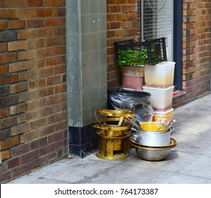 A photo of dirty dishes and food prep sitting out on the street