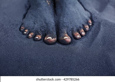 42fc84493 Photo of dirty woman bare feet in black sand. People relaxation
