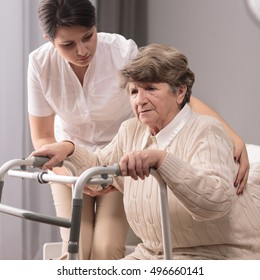 Photo of disabled elderly woman with zimmer having support