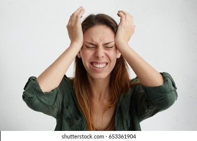 Photo of disappointed woman holding her hands on temples frowning face having wide opened mouth and closed eyes screaming in despair and terror. Woman regreting her act. Female in despair and shock