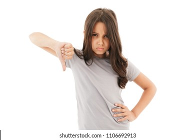 Photo of displeased girl standing isolated over white wall background with thumbs down.
