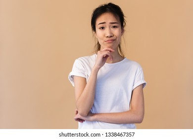 Photo of displeased japanese woman wearing basic t-shirt touching chin and pouting isolated over beige background in studio