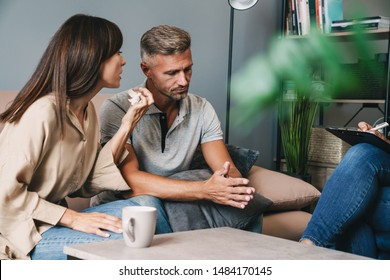 Photo of displeased nervous couple man and woman having conversation with psychologist on therapy session in room