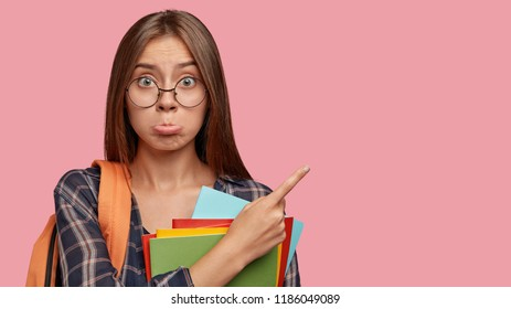 Photo of displeased offended Caucasian woman purses lower lip, carries rucksack, indicates with index finger at upper right corner, isolated over pink background. Youth and studying concept.