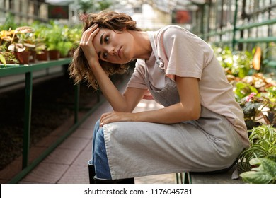 Photo of displeased tired woman gardener sitting over flowers plants in greenhouse.