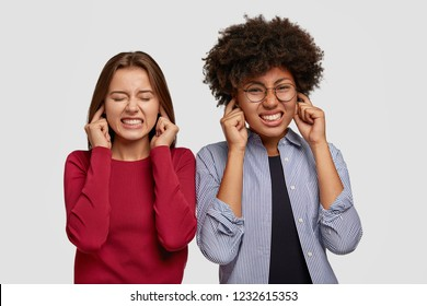 Photo of displeased women plug ears, ignore bad sound, clench teeth, stand closely to each other, isolated over white background. Indoor shot of annoyed females dont like rock music, not listen