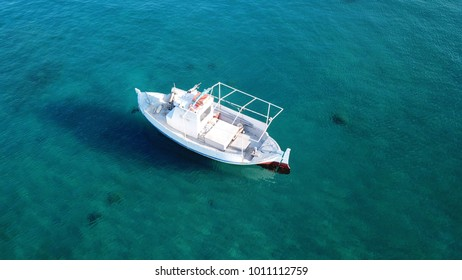 Photo of docked traditional boat with magnificent colours in deep blue clear waters of Mykonos island, Cyclades, Greece